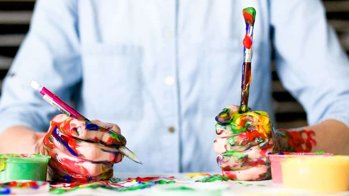 Man holding a paintbrush and a pencil covered in paint