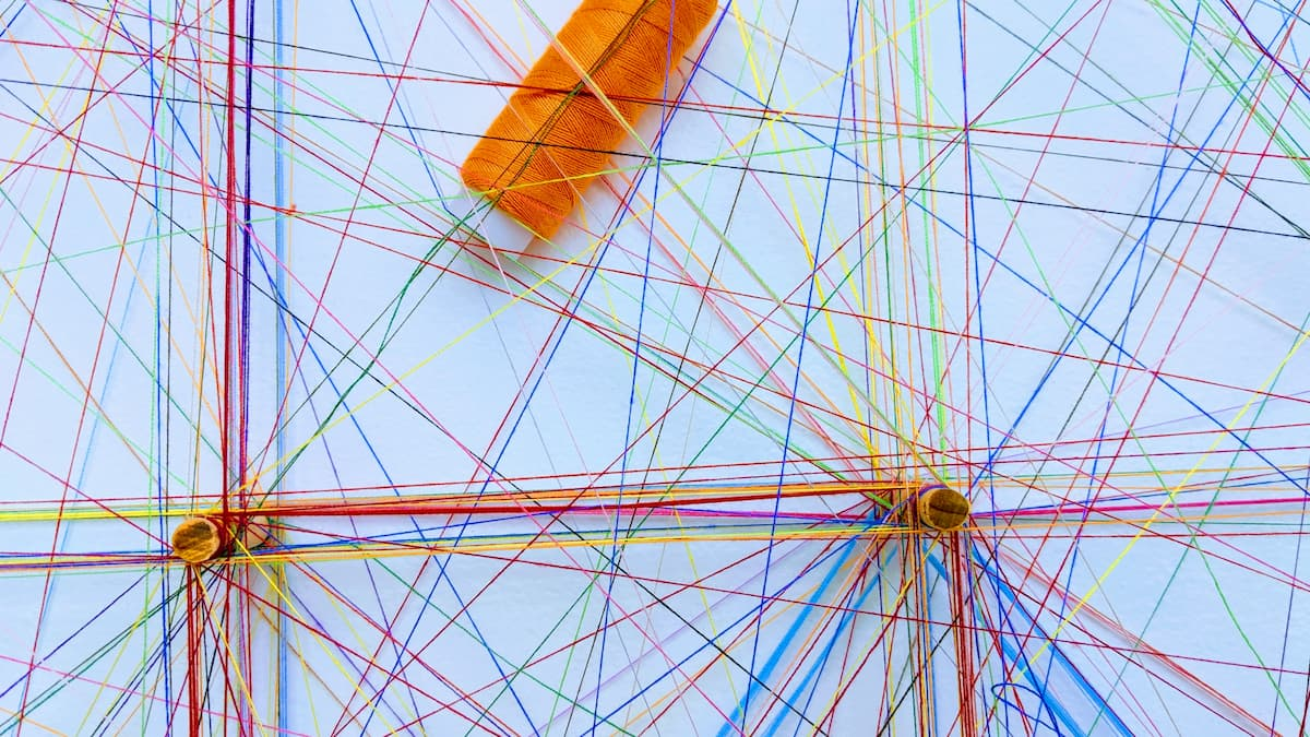 Multicoloured cotton threads in a network to illustrate the process of link building