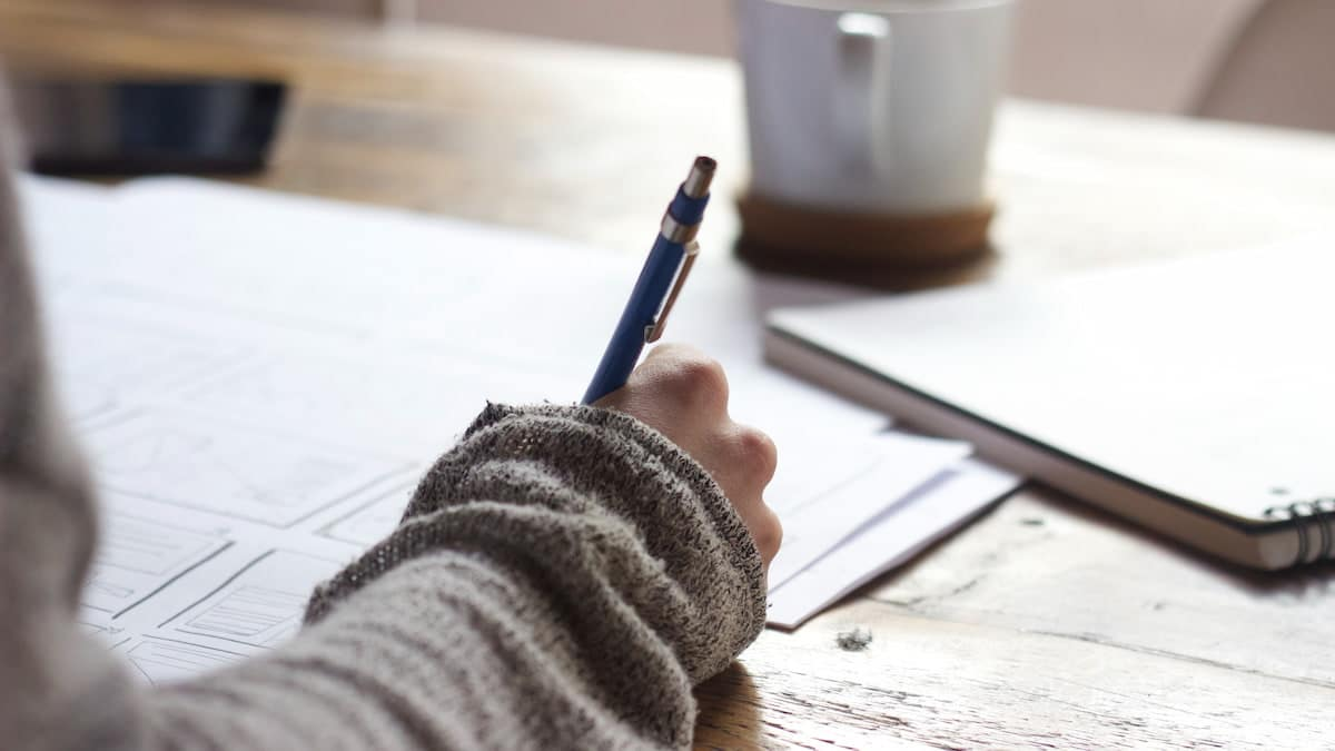 Person writing notes with a cup of coffee on a wooden desk