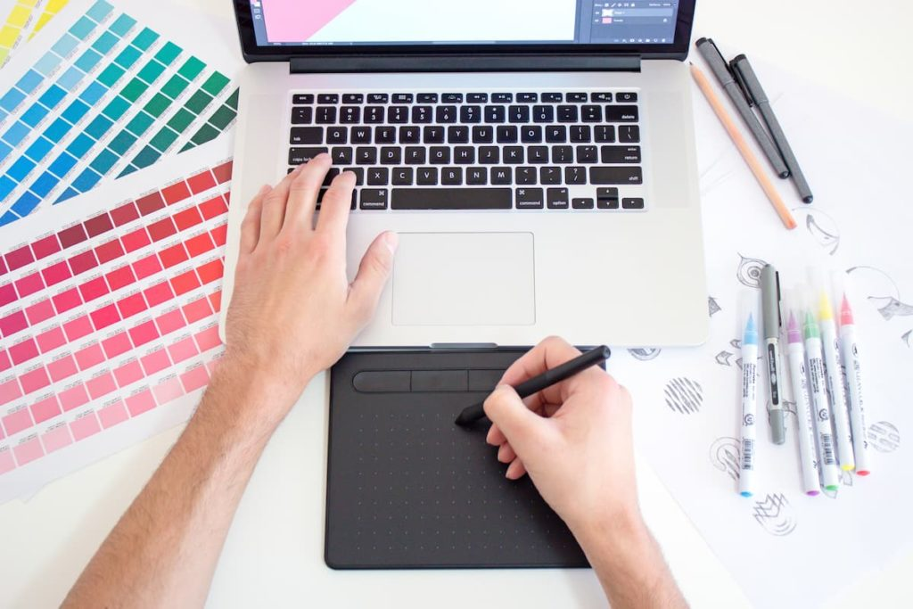 Designer drawing with design pad with laptop and colour palettes