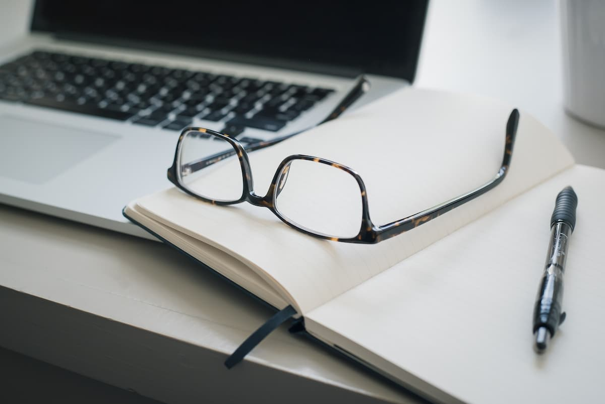 Glasses resting on notebook next to laptop