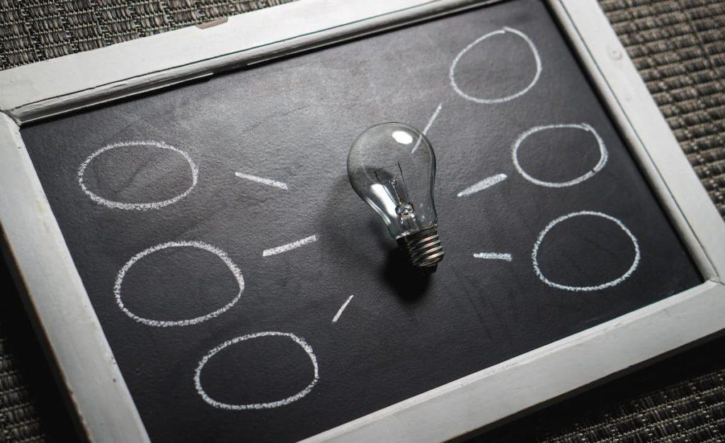 Clear lightbulb on blackboard with chalk